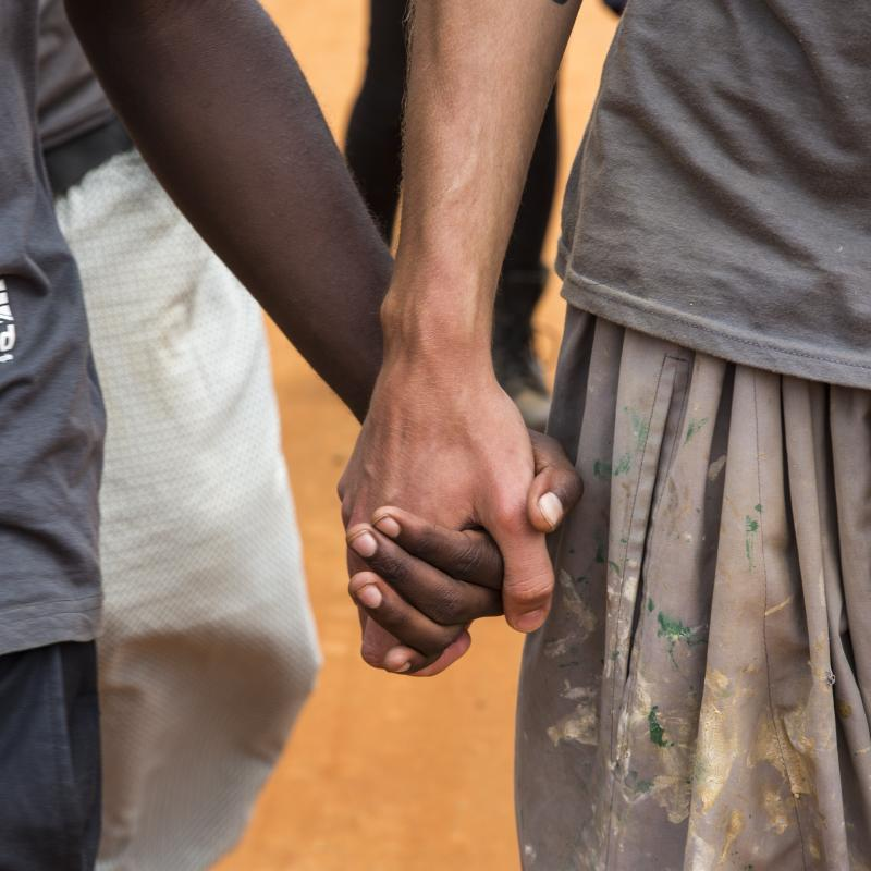 Two members of the team holding hands. The team of volunteers head out on a community outreach day knocking on doors and completing surveys as part of the ICS Raleigh SWASH (school water, sanitation and hygiene plan) project. Mbulu, Tanzania