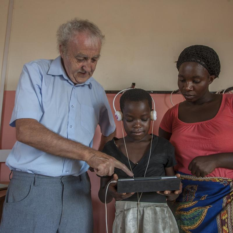 Volunteer Sean demonstrates tablet computer with teacher in Malawi