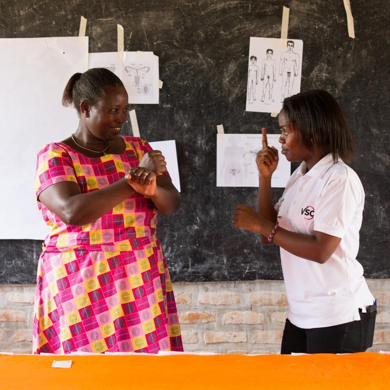 Brown Niyonsaba teaching sign language to community health worker Judith Mugirente