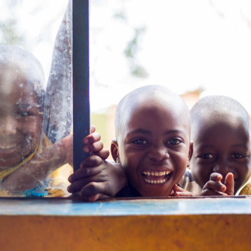 Children smiling at the window of Murama nursery school in Murama district, Rwanda.