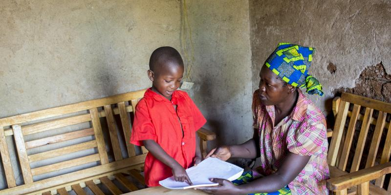 Antoinette shows her mother how she can write letters of the alphabet