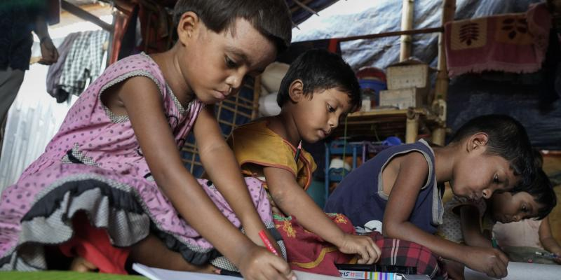 Four young Rohingya children sit on the floor and draw pictures at the home-based child friendly centre at Jamtoli.