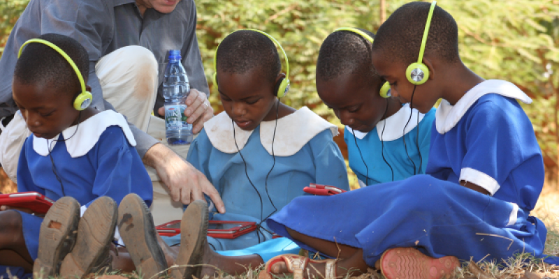 Andrew Ashe with children using tablets to support education in Malawi