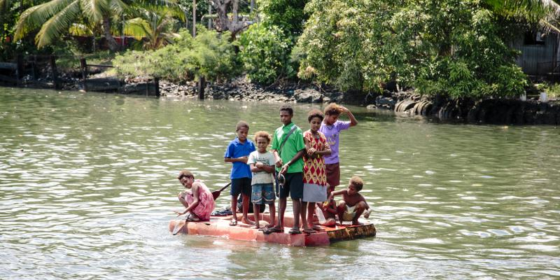 Children playing on a raft in Papua New Guinea