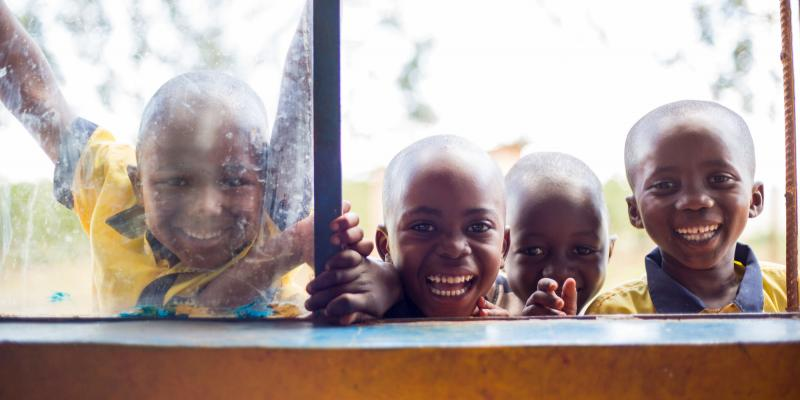 Children smiling at the window of Murama nursery school in Murama district, Rwanda.