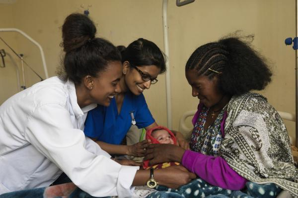 A midwife and VSO volunteer help a mother to position her newborn baby comfortably
