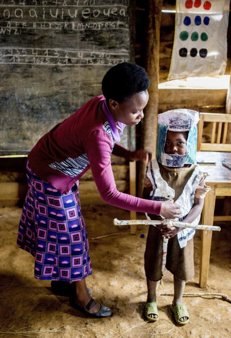 Teacher with child in moto costume made of rice sacks