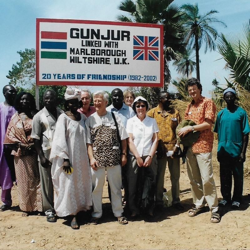 Dr Mick Maurice with local people in Gunjur, The Gambia in front of the sign declaring Gunjur linked to Marlborough (2002).