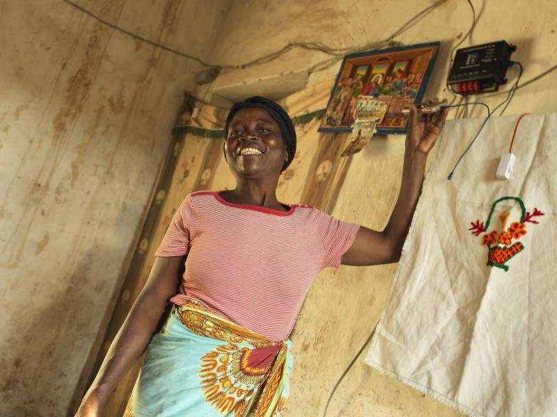 Woman with mobile phone charging business in Malawi   VSO2