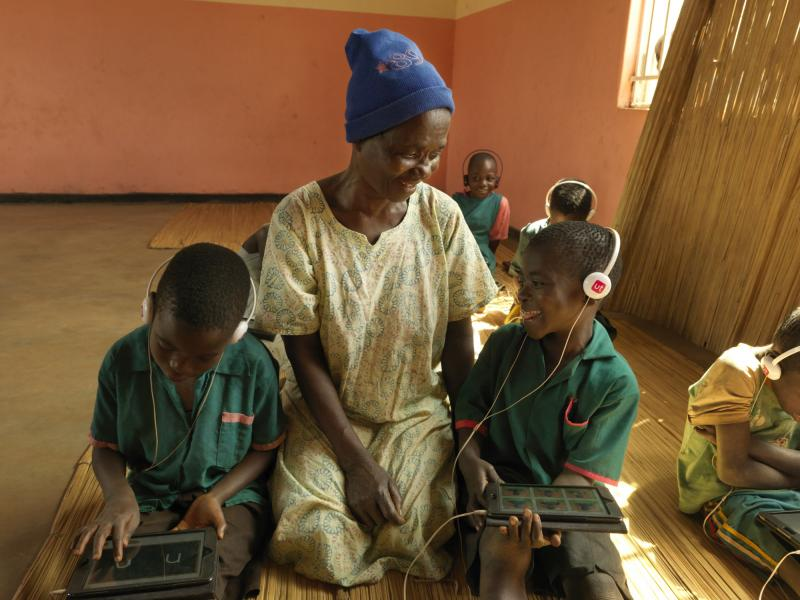 Edina with her grandson in a classrom with ipads in Malawi