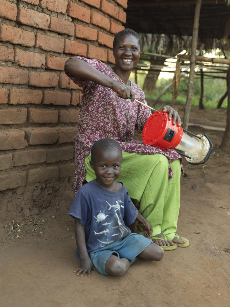 Solar engineer fixes a lantern with her young daughter
