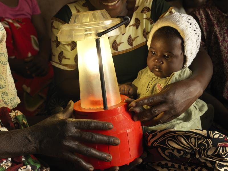 A baby with a solar lantern in Malawi