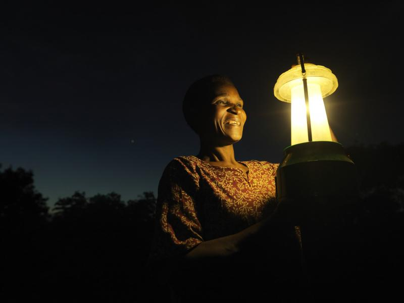Woman with solar lantern at night in Malawi Africa   VSO