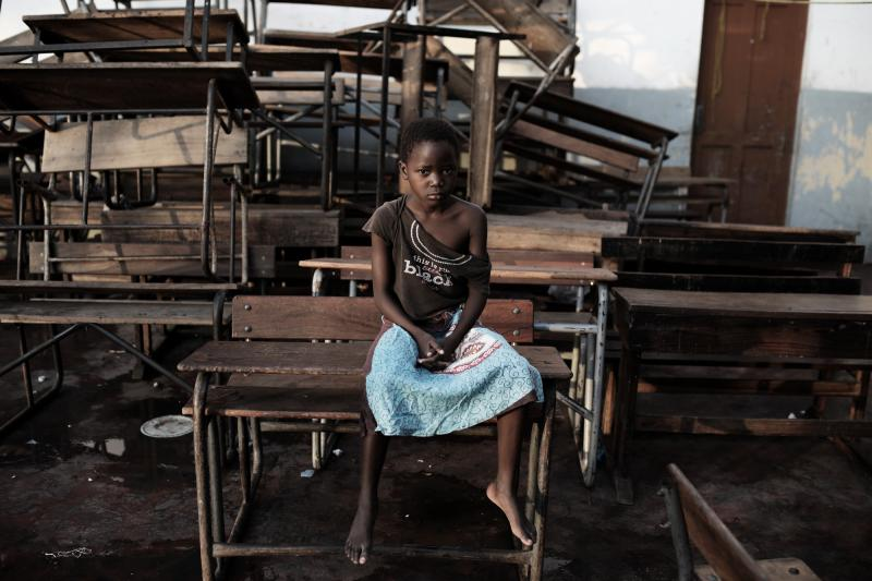 A child sits in an empty classroom in Beira