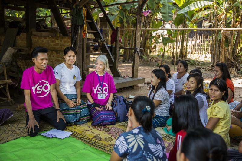 A community outreach session in progress, with education volunteer Ana Paula and national volunteer Kaung Khant.