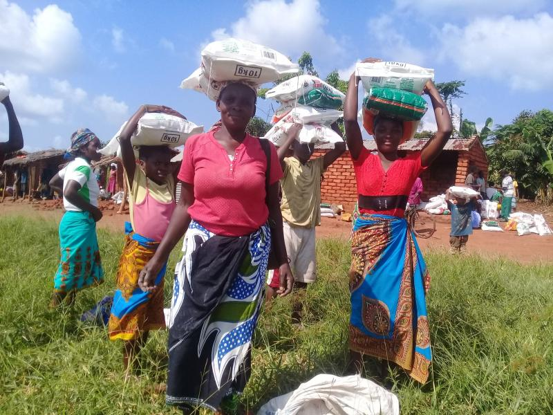 Women carry sacks of food aid on their heads