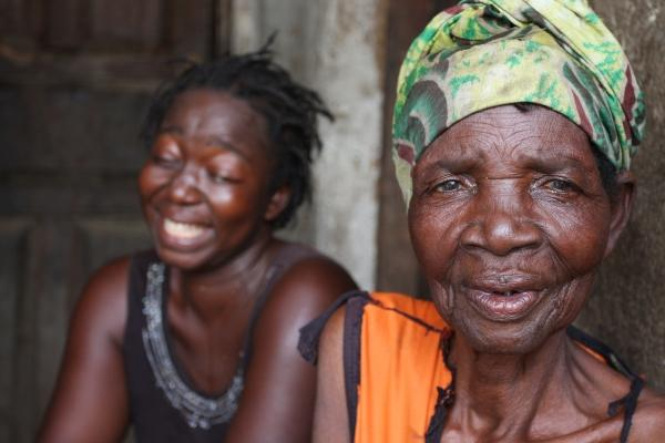Jennifer Kamara, who survived capture by the rebels during Sierra Leone's long civil war and then went blind, finds solace in her family life. Her grandmother (r), Sama Mansaray, tells a joke provoking a cackle from Jennifer outside their house in Binkolo